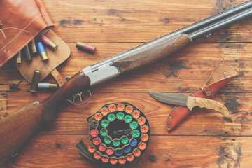 Acrylic Prints Hunting Hunting equipment. Shotgun, hunting cartridges and hunting knife on wooden table.