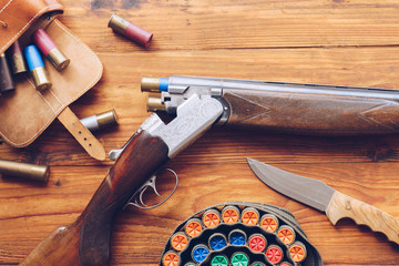 Door stickers Hunting Hunting equipment. Shotgun, hunting cartridges and hunting knife on wooden table.