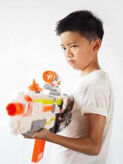 Asian boy holding a toy gun