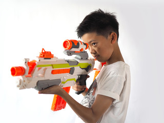 Asian boy aiming a toy gun.