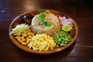 Obraz Kao Cluk Ka Pi or Mixed Cooked Rice with Shrimp Paste on the wooden round dish. Thai Traditional food. Selective focused. - fototapety do salonu