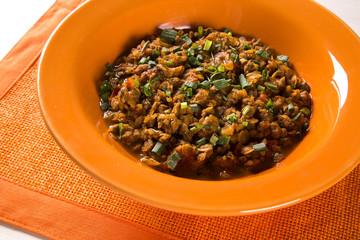 Sururu soup inside a orange plate. Brazilian dish.