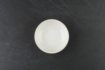 Bol blanco sobre plato de pizarra negra