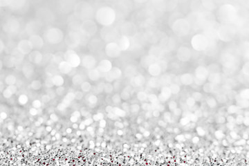 Silver white glittering Christmas lights. Blurred abstract festive background