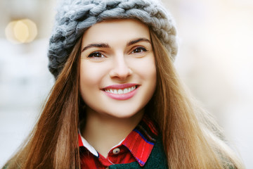 Outdoor close up portrait of young beautiful happy smiling girl posing in street. Woman with long hair. Model wearing winter hat, clothes