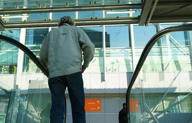 A man standing on an escalator.