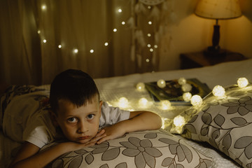 Portrait of Sad  boy lying in bed evening in dark against the background of lanterns
