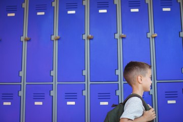 Boy carrying backpack against lockers