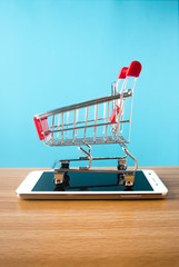 shopping cart with mobile smartphone on wood ground in business digital market