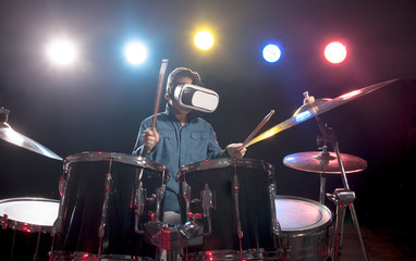 The boy learns to play drums, with glasses for virtual reality