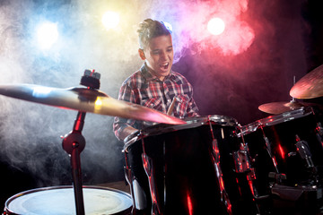 Drummer playing the drums with smoke