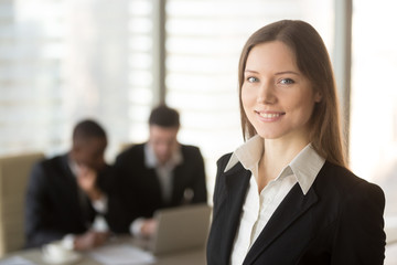 Portrait of beautiful millennial businesswoman looking at camera, multinational businessmen using laptop on background. Young happy female business leader or job candidate posing at meeting in office