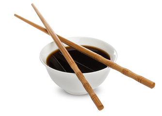 Soy sauce and chopsticks isolated on white background