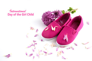 pink kid shoes, flower and petals isolated on a white background, text International Day of the Girl Child, concept date 11 Octobe