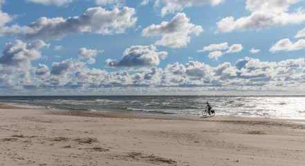 Empty beach under cloudy sky with lonely biker riding