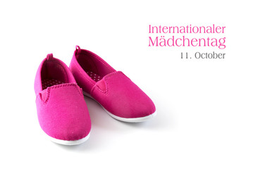pink kid shoes isolated on a white background, german text  Internationaler Maedchentag 11 October, that means international day of the girl child, copy space