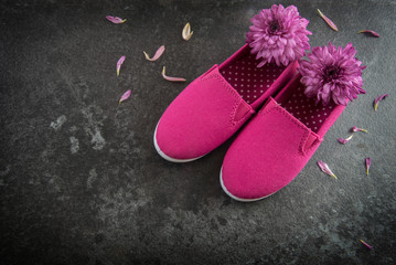 pink kid shoes and flowers on a dark slate background, concept International Day of the Girl Child on 11 October, copy space, selected focus