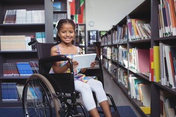 Girl on wheelchair smiling while holding digital tablet