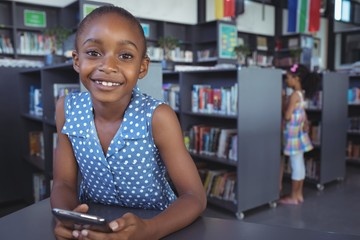 Smiling girl with mobile phone at desk in library