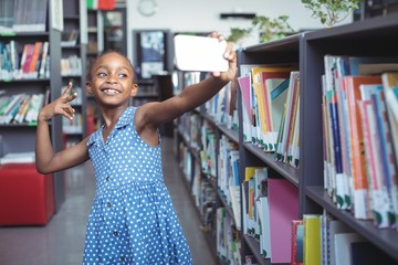 Smiling girl taking selfie by bookshelf in library