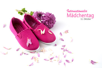 pink kid shoes, a flower and petals isolated on a white background, german text Internationaler Maedchentag, that means  International Day of the Girl Child, concept date 11 Octobe