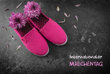 pink kid shoes and flowers on a dark slate background, german text  Internationaler Maedchentag, that means International Day of the Girl Child,  date concept 11 October, copy space