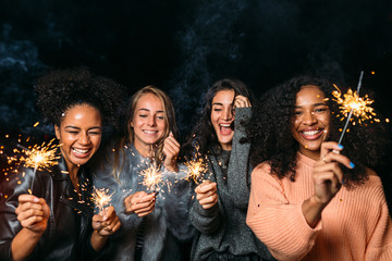 Young friends enjoying a party. Happy women holding sparklers.