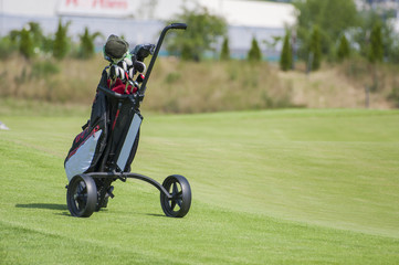 Golf trolley with clubs in golf curse