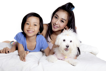 Mother and child play with dog on studio