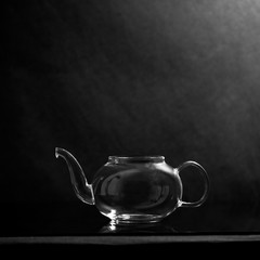 Glass teapot with tea and steam on dark background