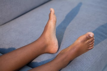 Low section of boy lying with shadow on sofa at home