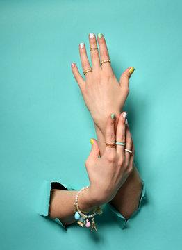 Beautiful woman hands with yellow pink white pattern nail polish