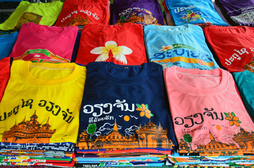 Colorful t-shirts with Lao tourist attractions screen printing sold at souvenir shop in Vientiane, capital city of Lao PDR.
