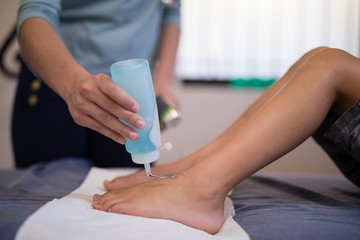 Female therapist pouring scanning gel on feet of boy