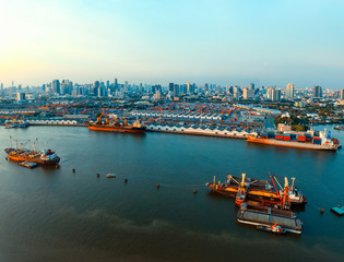 aerial view of commercial ship and container dock  in chaopraya river with urban skyline in bangkok thailand capital