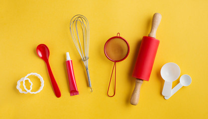 Different baking tools on yellow background, top view.