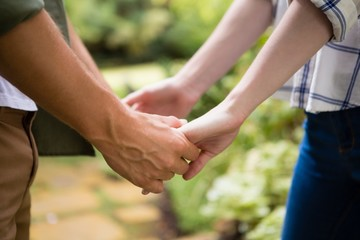Mid-section of couple holding hands