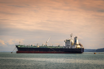 An empty tanker is in the bay at anchor.