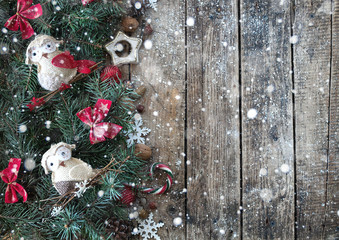 Christmas wooden background with branches of Christmas tree and Christmas decorations with snow. Christmas design. Copy space