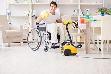 Disabled man with vacuum cleaner at home