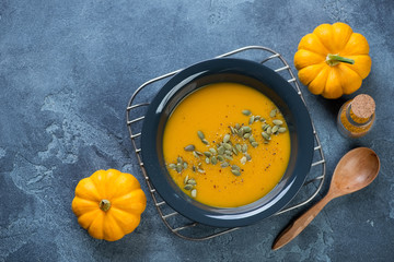 Plate of freshly made pumpkin soup on a metal cooling rack, flat-lay on a blue stone background, horizontal shot with space