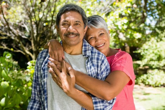 Senior couple embracing each other in garden on a sunny day