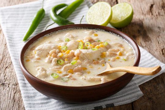 Homemade white chili chicken with beans, lime and corn close-up. horizontal