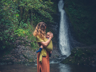 Mother with baby standing by waterfall