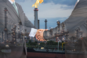 Businessmen handshaking in front of oil refinery plant. Agreement, Collaboration and  for oil and gas business concept.