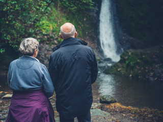 Senior couple admiring waterfall
