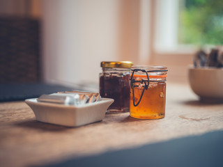 Jars of jam and butter on table