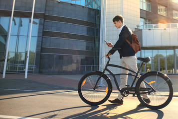 Young businessman with bicycle and smartphone on city street.