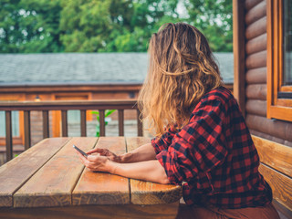Young woman using smart phone on porch