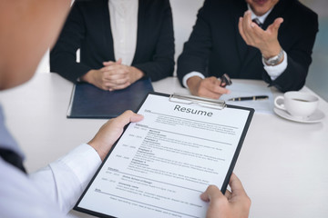 Interviewer or Board reading a resume during a job interview, Employer interviewing a young male job seeker for recruitment talking in modern office, employment and recruitment concept